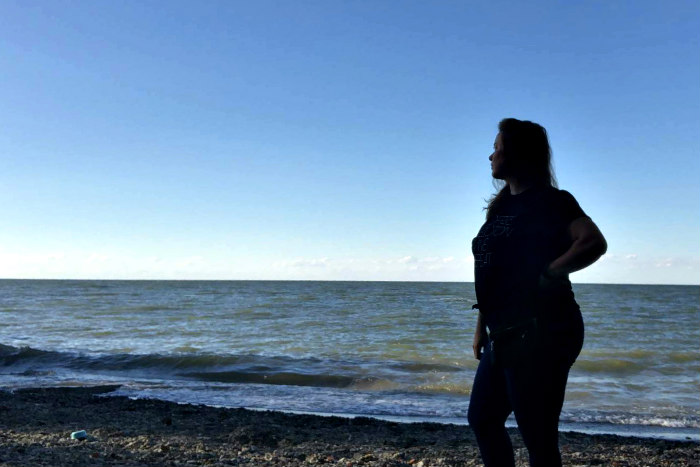 Silhouette of a woman with her hand on her hip staring out over a body of water