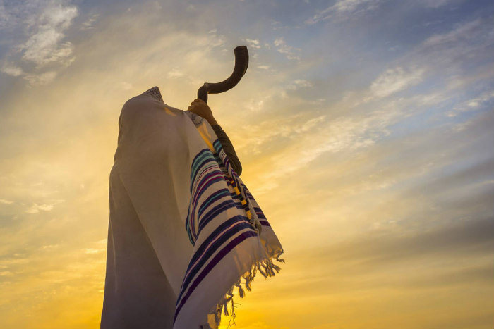 View from behind of a person blowing a shofar into the sunset while wearing a prayer shawl that covers their head and back