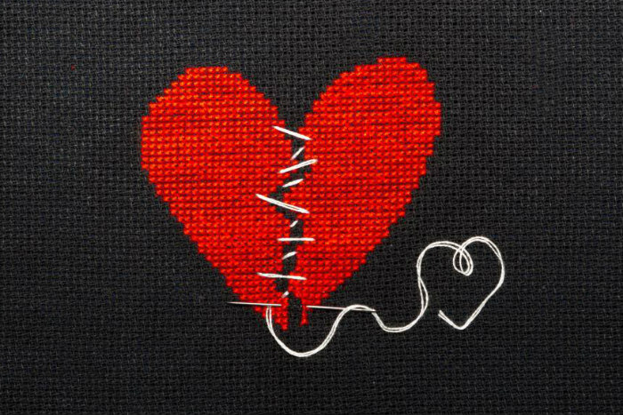 Cross stiched image of a broken heart being sewn back together with white thread