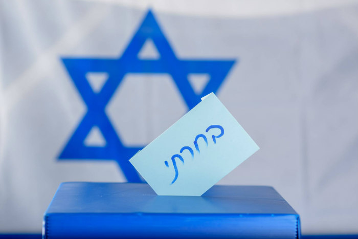 Blue ballot box in front of an Israeli flag