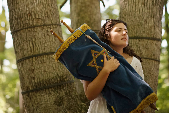 Young woman holding a Torah against trees