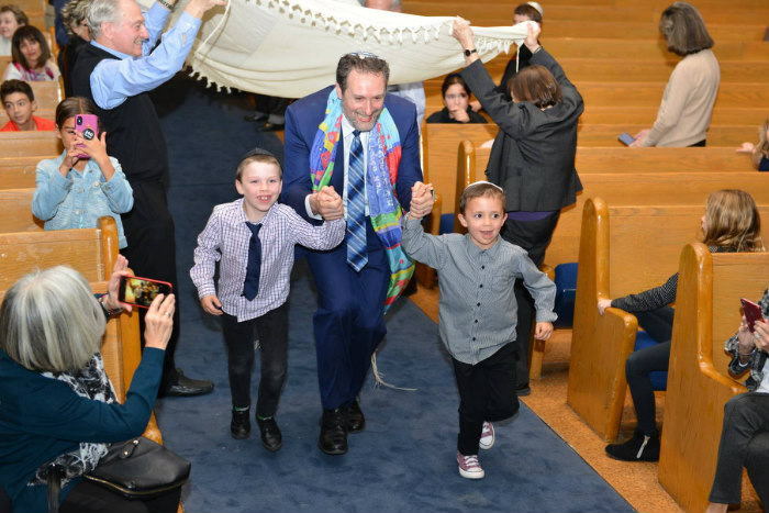 Rabbi Michael Dolgin holds hands with two young children beneath a prayer shawl in the middle of synagogue pews
