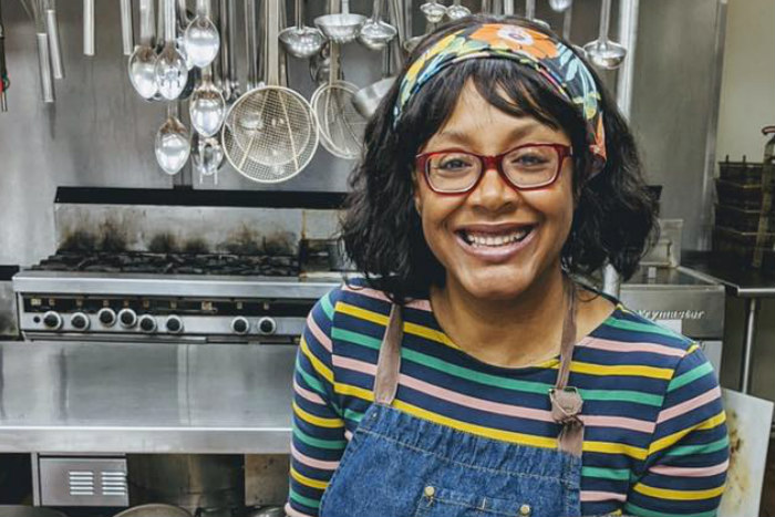 Chef Marisa Baggett smiles in front of a kitchen setting