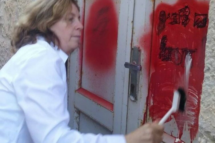 Anat Hoffman scrubs graffiti off of a cement wall