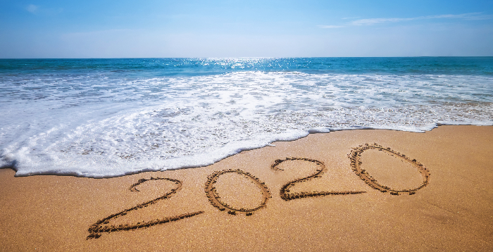 Beach with 2020 written in the sand and a wave coming to wipe it out