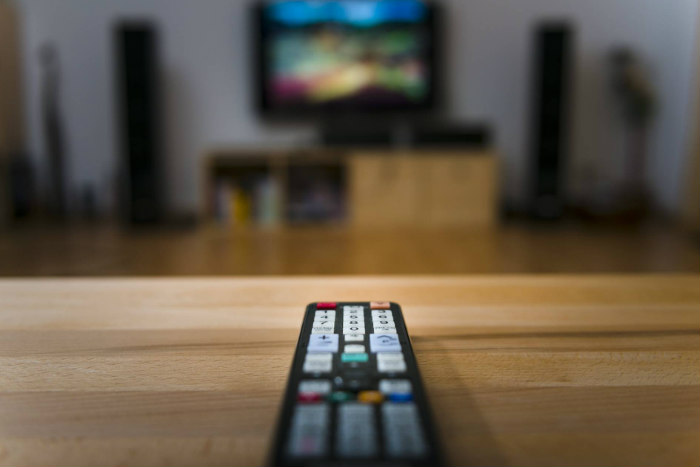 A remote control pointed at a blurry TV in the background