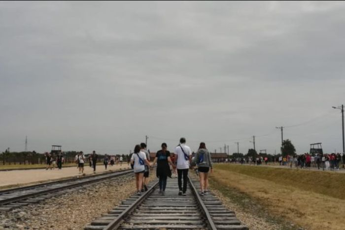 Teenagers walking down railroad tracks while visiting a concentration camp