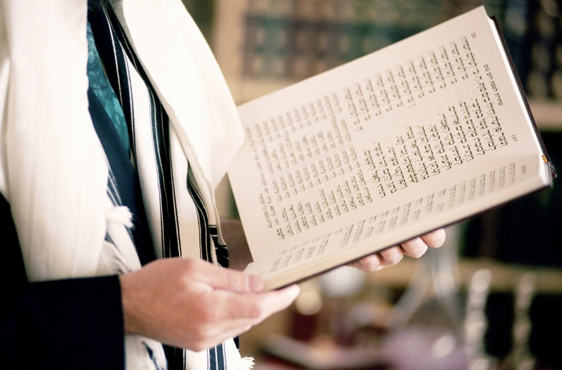 boy holding a Siddur, or a Jewish prayer book, to practice his beliefs and participate in a Jewish ritual.
