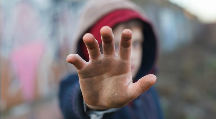 Child covering his face by holding a dirty hand up to the camera