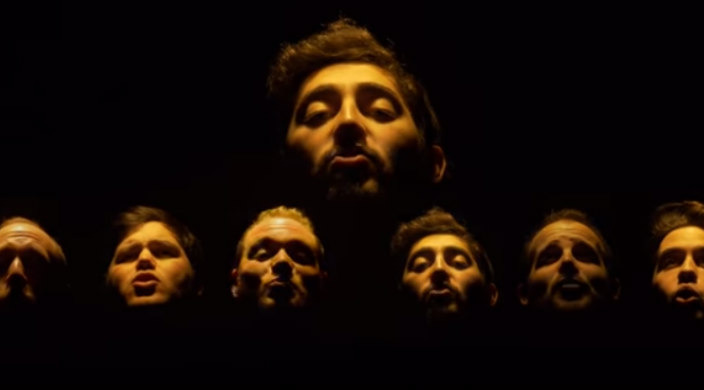 Screencap from Six13 video of its members faces illuminated against a black background