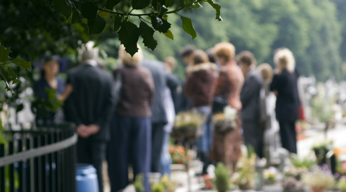 Group of people gathered at a gravesite in a cemetery