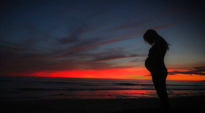 Silhouette of a pregnant person against a brightly colored sunset