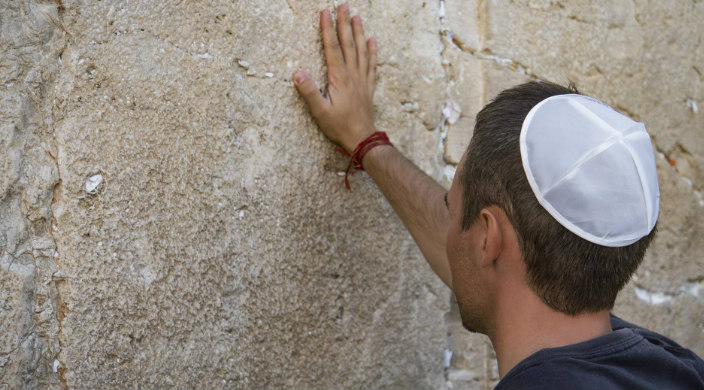 Man in a kippah with his back to the camera and his hand on the Western Wall