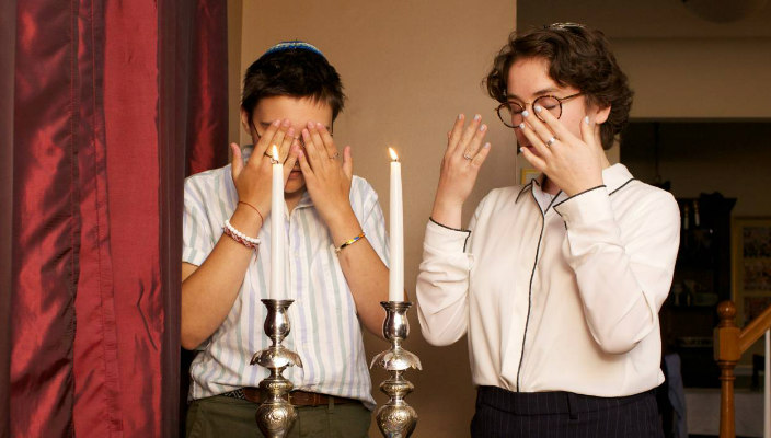Jewish couple blessing the candles