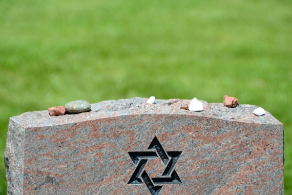 Headstone engraved with a Star of David with small stones on top