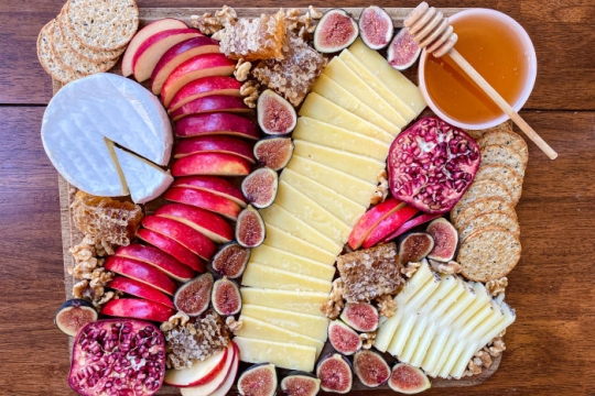Decorative Rosh HaShanah cheese board featuring cheese apples honey crackers and walnuts