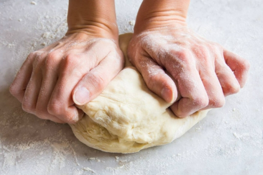 Hands kneading a ball of dough on a white surface