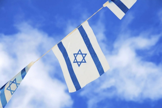 String of Israeli flags against a cloudy blue sky