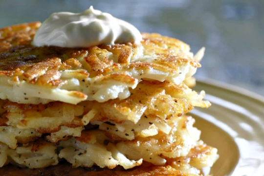 Pile of potato pancakes topped with a dollop of sour cream