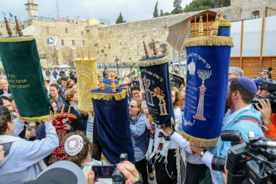Group of people holding up Torah scrolls in a protest at the Western Wall