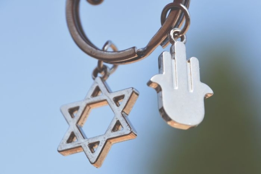 Silver star of David and a hamsa hanging from a key ring