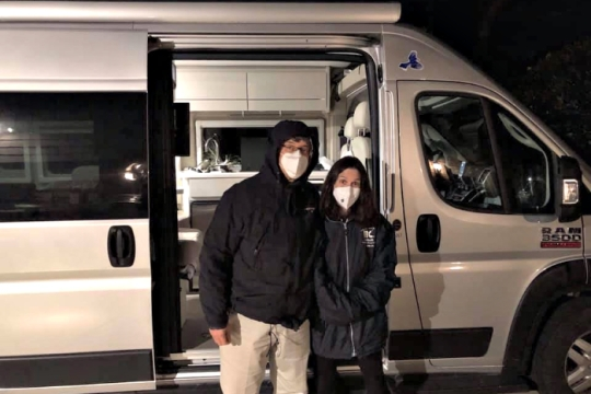 Rabbi Jeff and Mindy Glickman stand together in face masks in front of their white RV