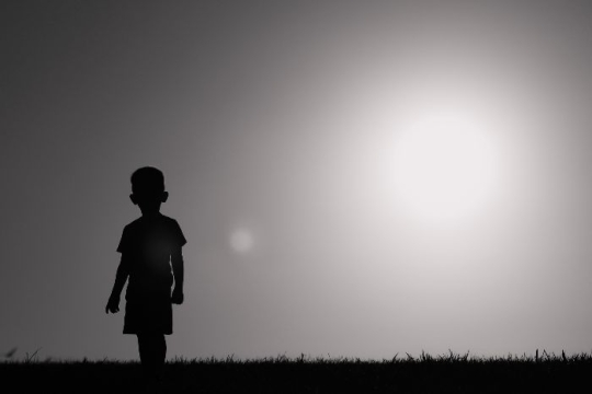Silhouette of a young boy standing alone against a sunset