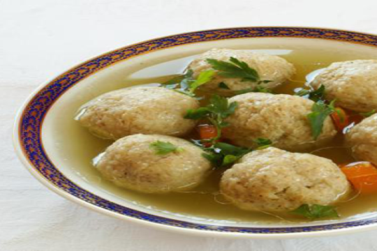 White bowl with blue edge containing soup crowded with matzah balls