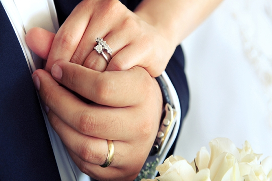 Married couple holding hands, wearing wedding bands
