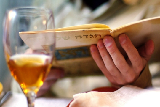 Person at a seder table reading haggadah; glass of wine in foreground