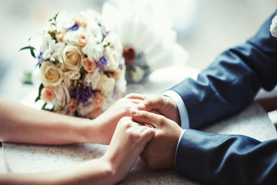 couple holding hands and bouquet of flowers