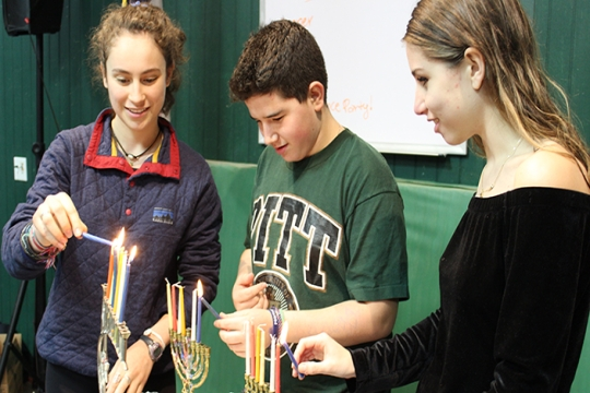three teens each lighting a hanukkiyah