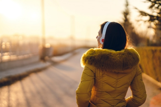 Women wearing a yellow coat facing away from the camera wearing a pair of headphones and looking out over a dock