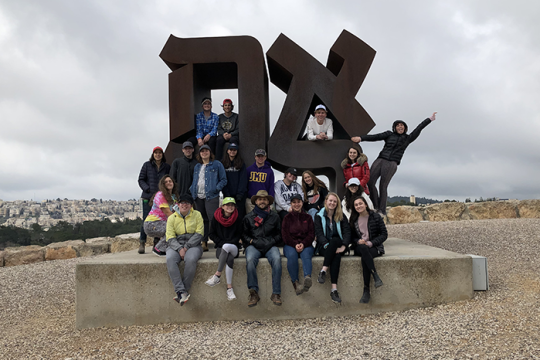Heller HIgh Students posing in front of the Ahava sign
