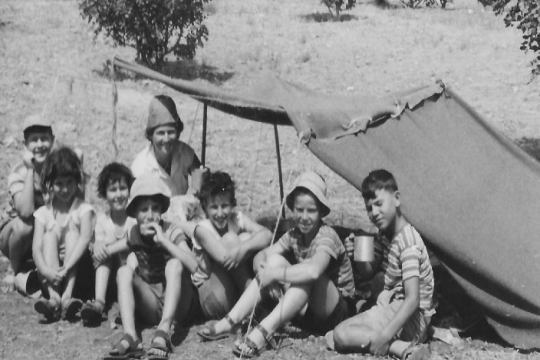Black and white image of a group of smiling children beneath a small tent in a desert setting