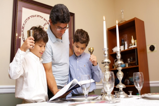Father and young sons reading from a prayerbook as the light Shabbat candles at a kitchen table