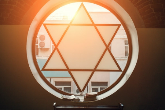 Circular stained glass window featuring a Star of David with open books sitting in the window sill